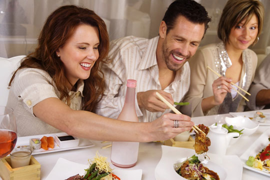 man eating confidently with two women